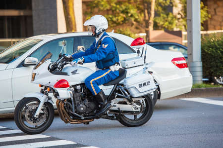 TOKYO, JAPAN - OCTOBER 31, 2017: A policeman on a motorcycle on a city street. Copy space for text