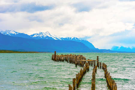 Wooden pillars of the old pier, Puerto Natales, Chile. Copy space for text Standard-Bild