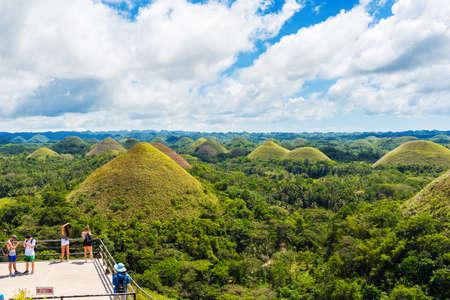 BOHOL, FILIPPIJNEN - FEBRUARI 23, 2018: Mensen op de achtergrond van chocoladeheuvels op zonnige dag