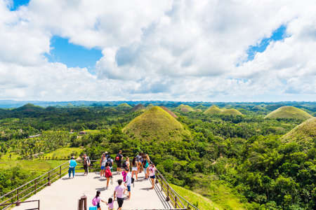 BOHOL, PHILIPPINES - FEBRUARY 23, 2018: People on the background of Chocolate hills on sunny day