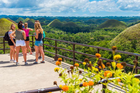 BOHOL, PHILIPPINES - FEBRUARY 23, 2018: Group of people on the viewing platform on the background of Chocolate hills. With selective focus