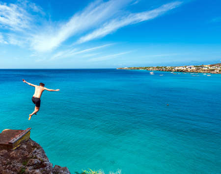 Man jumping off a cliff, Westpunt, Curacao, Netherlands. Copy space for text