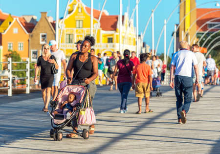 WILLEMSTAD, NETHERLANDS - JANUARY 23, 2018: Woman with a stroller on a city street. With selective focus