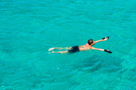 CURACAO, NETHERLANDS - JANUARY 23, 2018: A man swims in clear water. Copy space for text