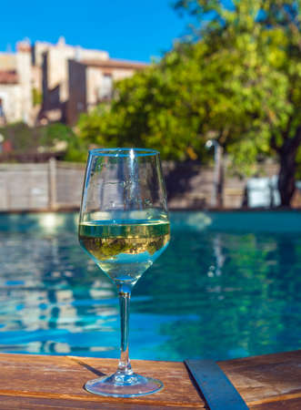 A glass of wine on the background of the pool in Siurana, Tarragona, Spain. With selective focus. Close-up