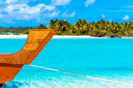 Wooden carved boat on a sandy beach in Aitutaki island, Cook Islands, South Pacific. With selective focus 免版税图像