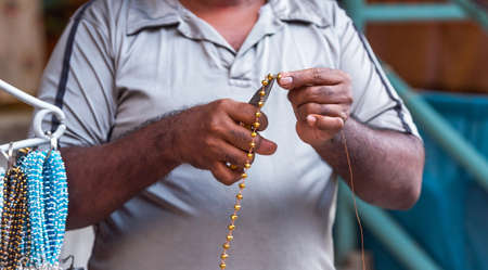 Gold beads in male hands, Puttaparthi, India. With selective focus Stockfoto