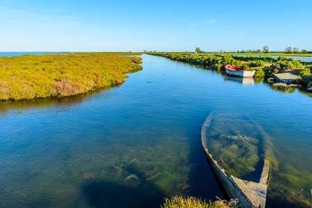 Boat on a Canal in Ebro Delta estuary and wetlands, Tarragona, Catalunya, Spain.
