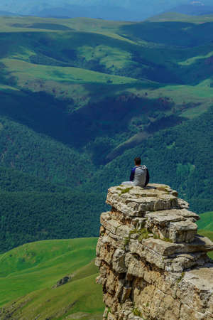 Man on a Rock at the Amazing Bermamyt Plateau. Caucasus Elbrus Region in Russia Summer Landscape with green Meadow, Panorama dramatic Sky Stock Photo