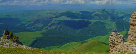 Woman sit on a Rock at Beautiful Amazing Bermamyt Plateau. Caucasus Elbrus Region in Russia Summer Landscape with green Meadow, Panorama