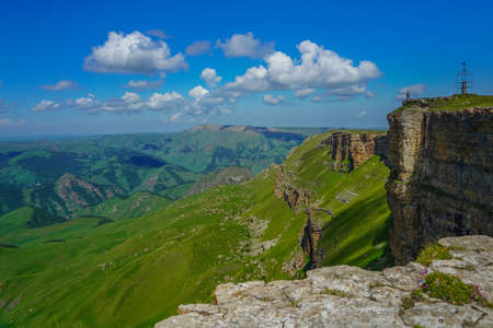 Man Stands on the Abyss at the Amazing Bermamyt Plateau. Caucasus Elbrus Region in Russia Summer Landscape with green Meadow, Panorama dramatic Sky