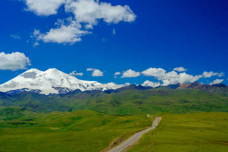 Panorama Road Leading to Mount Elbrus with Green Meadows at Summer. North Caucasus, Russia Stock Photo