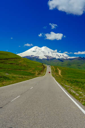 Panorama Road Leading to Mount Elbrus with Green Meadows at Summer. North Caucasus, Russia, Vertical Stock Photo