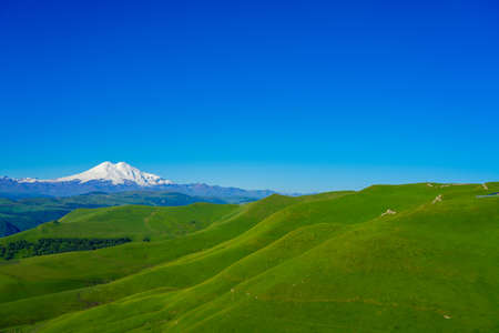 Amazing Background Elbrus and Green Meadow Hills at a Summer Day. North Caucasus, Karachay-Cherkessia, Russia Stock Photo