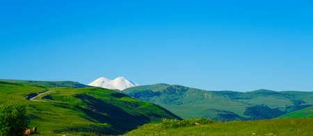 Amazing Elbrus and Green Meadow Hills at a Summer Day. North Caucasus, Karachay-Cherkessia, Russia, panorama