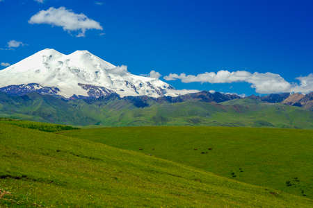 Elbrus and Green Meadow Hills with blue Sky Stock Photo