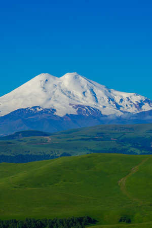 Elbrus and Green Meadow Hills at a Summer Day. Vertical Stock Photo