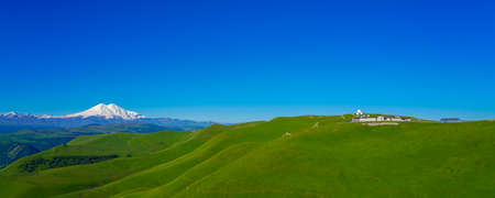 Green Meadow Hills background Elbrus at a Summer Day. Panorama