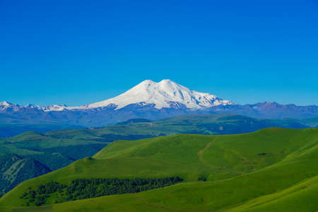 Green Meadow Hills background Elbrus at a Summer Day. North Caucasus, Russia Stock Photo