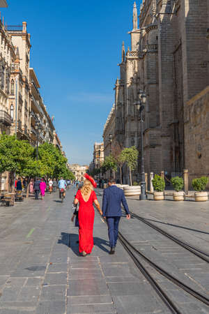 SEVILLE, SPAIN - OCTOBER 17, 2020: A couple of Flamenco dancer in red dress walking at the church in Seville, Andalusia, Spain, vertical Editorial