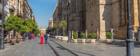 SEVILLE, SPAIN - OCTOBER 17, 2020: A couple of Flamenco dancer in red dress walking at the church in Seville, Andalusia, Spain, panorama Editorial