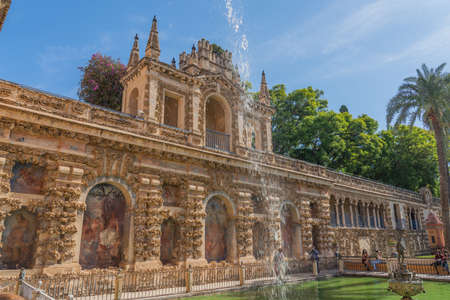 SEVILLE, SPAIN, OCTOBER 18.2020: The Fountain with the historical building with painting in the yard of the Real Alcazar Palaces in Seville, Andalusia