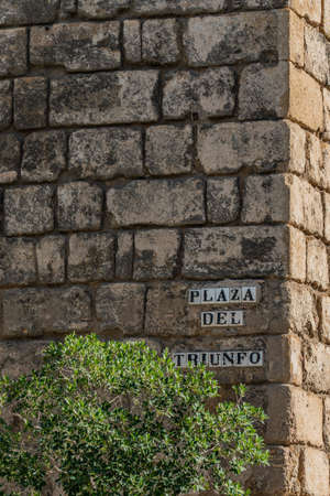 Street name sign on Plaza del Triunfo in Seville, Andalusia, Spain.