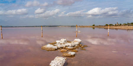 Rocks in a pink salt lake Laguna Rosa, Torrevieja, reflection on water from clouds, panorama