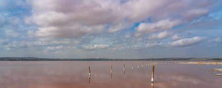 Wooden posts in the pink salt lake with reflection on water from clouds, Laguna Rosa, Torrevieja, panorama Banco de Imagens