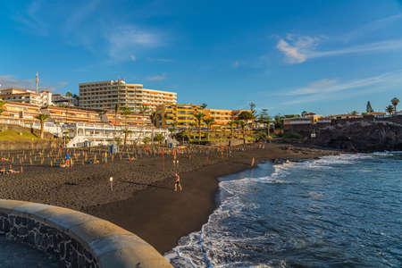 PUERTO DE SANTIAGO, SPAIN - NOVEMBER 09.2020: Playa de la Arena is a beach with black volcanic sand during sunset in Puerto de Santiago, Tenerife, Spain