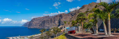 A colorful painted fishing boat on display near the ocean in Los Gigantes, Tenerife, Canary Islands, a picture postcard scenic view of the island. panorama view