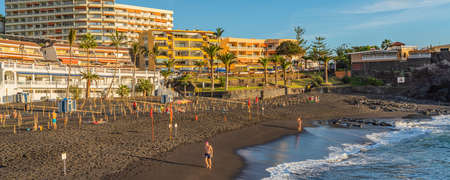 PUERTO DE SANTIAGO, SPAIN - NOVEMBER 09.2020: Playa de la Arena is a beach with black volcanic sand during sunset in Puerto de Santiago, Tenerife, Spain panorama view