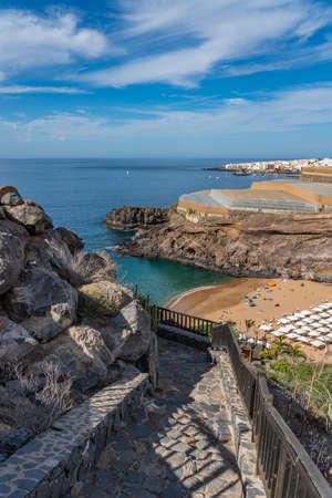 Playa de Abama with tourists, stone stairs, parasol. Tenerife, Canary Island, vertical