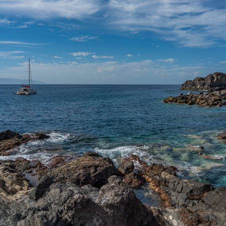 Playa de Abama with a boat and a tourist snorkeling in clear water, Tenerife, Canary Island, Spain