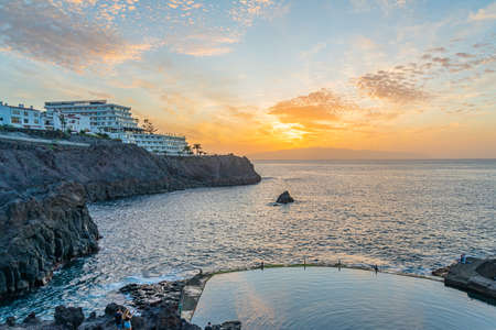 People during sunset at the natural Pool beside the Cliffs of Los Gigantes in Tenerife, Acantilados de los Gigantes, Canary islands, Spain 免版税图像