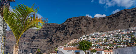 View of Puerto de Santiago with the typical Building, Tenerife, Canary Islands, Spain, background Los Gigantes, panorama 免版税图像