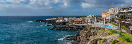 Tropical island of Tenerife. Panorama of the Coastline with buildings with pool on the island of Tenerife. Background blue sky color