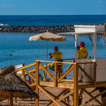 LOS CRISTIANOS, TENERIFE, CANARY ISLAND, SPAIN, DECEMBER 02. 2020: Playa del Camison beach. It is a small beach with straw parasols in Tenerife island, vertical 新闻类图片
