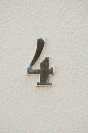 adress: Number four house adress plate. White wall