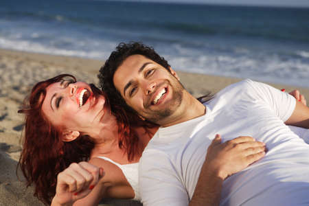 Young couple at the beach laughing. Look at our light boxes for similar images