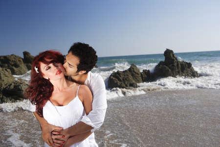 is playful: Joven pareja en la playa del hombre besando el escote de la mujer.  Foto de archivo