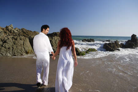 Young Couple at the beach holding hands and walking in front of rocks and waves photo