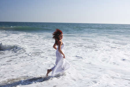 woman beach dress: Woman wearing a white dress running in the waves.
