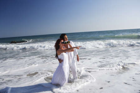 Young couple at the beach in the water pointing and looking through binoculars. photo