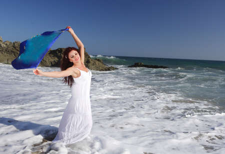 scarf beach: Young Woman at the beach holding   Stock Photo