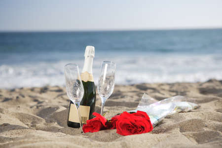 casal: Garrafa de champanhe, vidros, rosas na praia na areia
