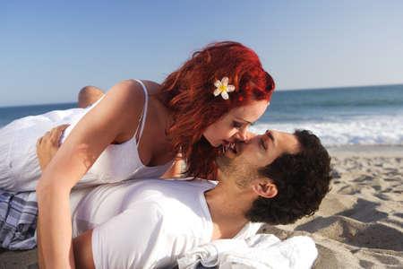 parejas enamoradas: Joven pareja en la playa a besar, feliz e �ntimo de configuraci�n.