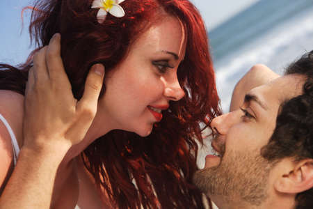 Young couple at the beach about to kiss, happy and intimate setting.  photo
