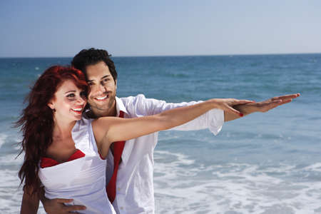 Young Couple at the beach holding hands pointing right photo
