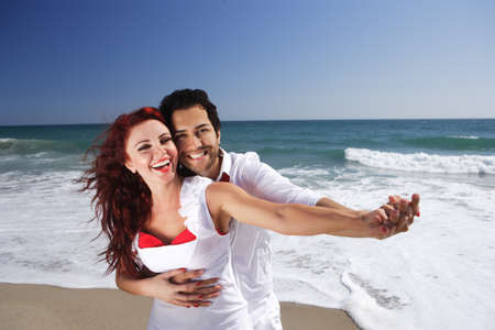 Young Couple at the beach holding hands pointing right